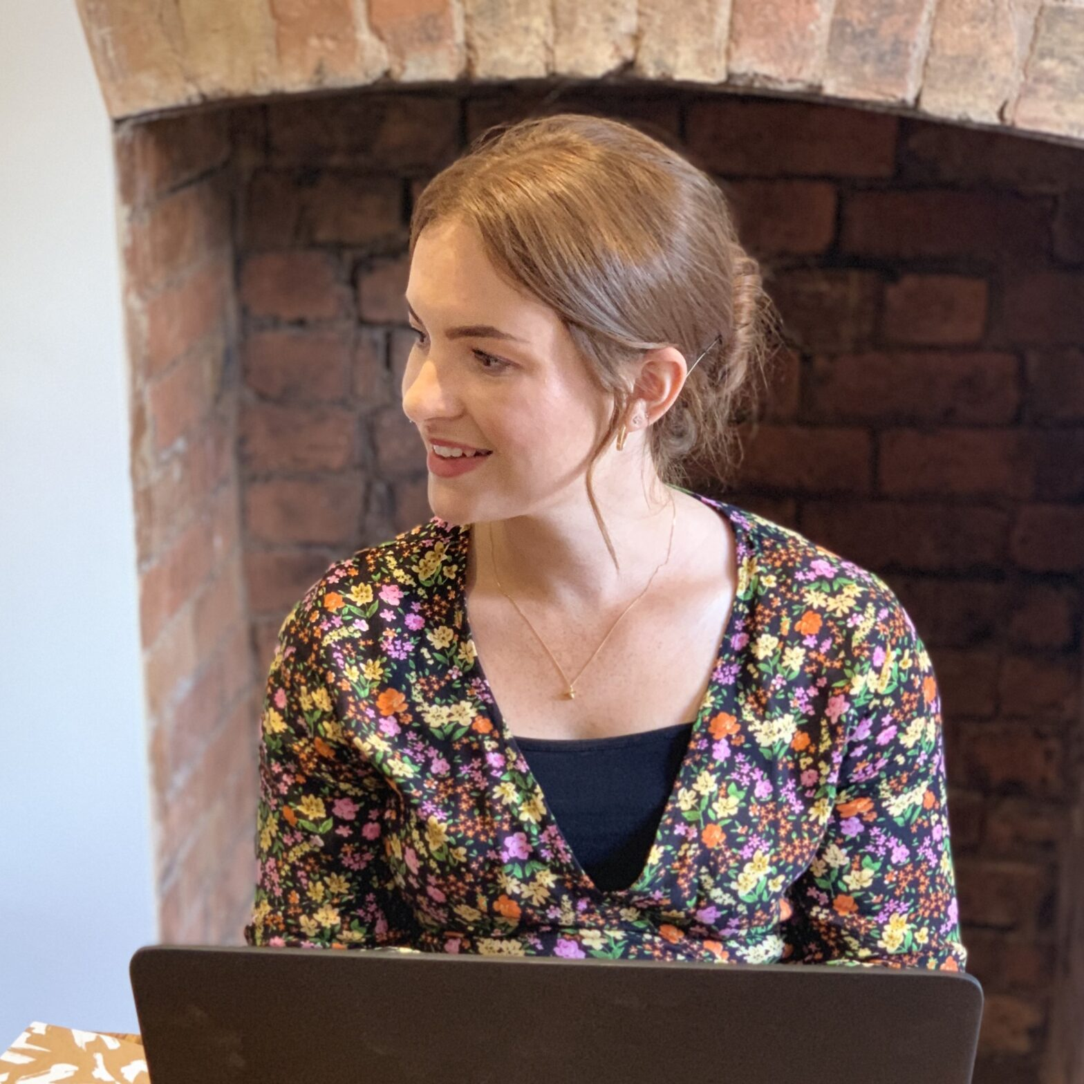 Email: The gold dust in your marketing plan. Danielle smiling and writing an email