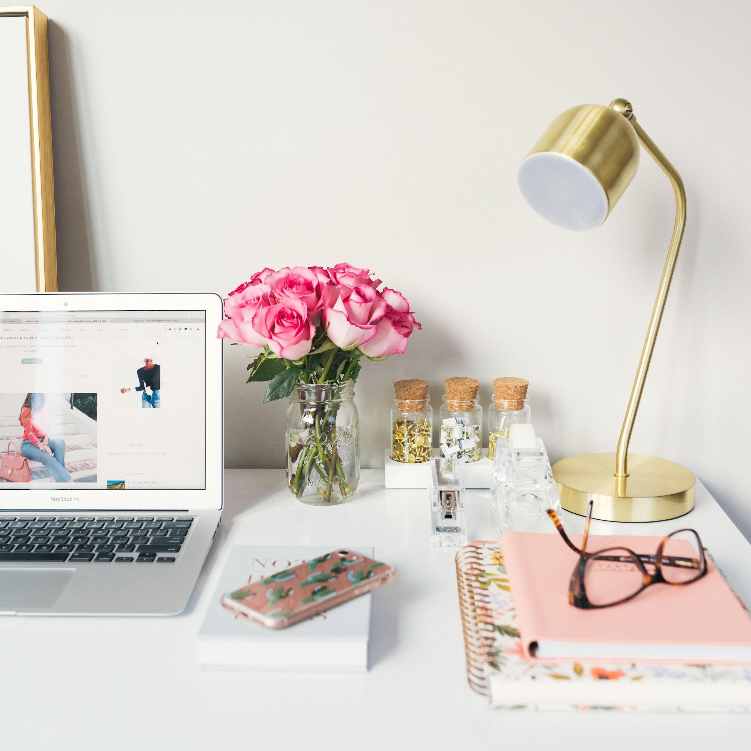 How to get out of a content creation rut - desk set up with flowers, gold lamp, books, laptop and glasses